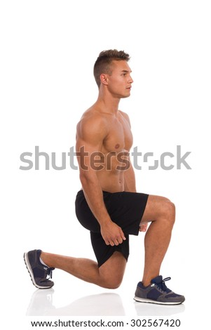 Muscular man does a split squat, side view. Full length studio shot isolated on white. - stock photo