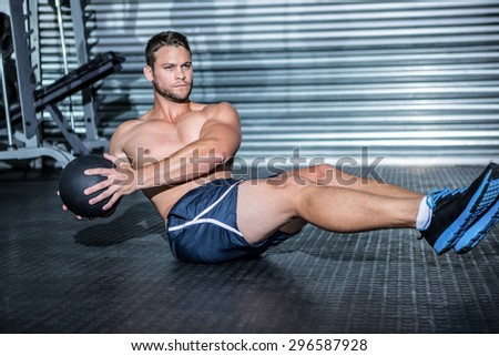 Muscular man doing exercise with medicine ball in crossfit gym - stock photo