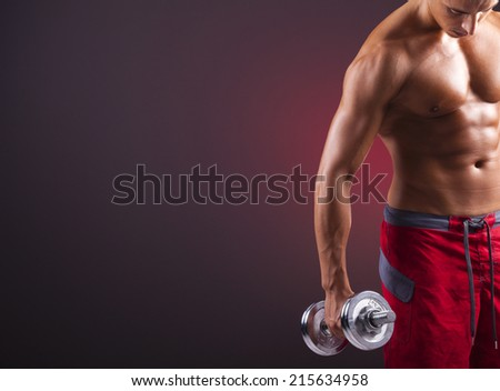 Muscular man doing exercises with dumbbells on black background - stock photo