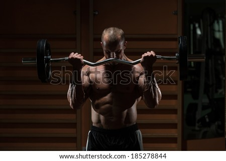 Muscular Man Doing Heavy Weight Exercise For Biceps - stock photo