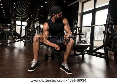 Muscular Man Doing Heavy Weight Exercise For Biceps With Dumbbells In Modern Gym - stock photo