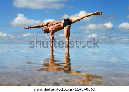 Muscular man doing lateral stretching yoga exercise into the sea water - stock photo