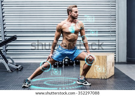 Muscular man doing leg stretchings against fitness interface - stock photo