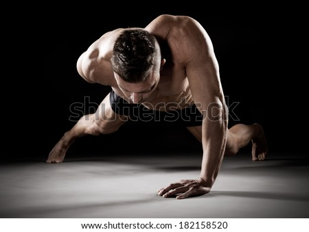 Muscular man doing push-ups on one hand against dark background. - stock photo
