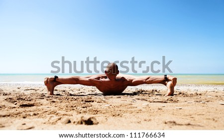 Muscular man doing stretching yoga pose at the sand beach - stock photo