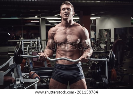 Muscular man during his workout in gym - stock photo