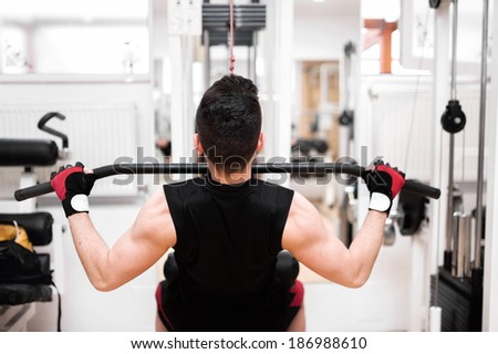 Muscular Man Exercising In Gym - Bodybuilder Doing Heavy Weight Exercise For Back and ticeps - stock photo