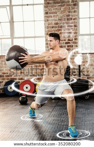Muscular man exercising with medicine ball against fitness interface - stock photo
