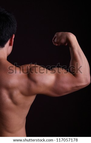 Muscular man flexing biceps to show how strong he is. - stock photo