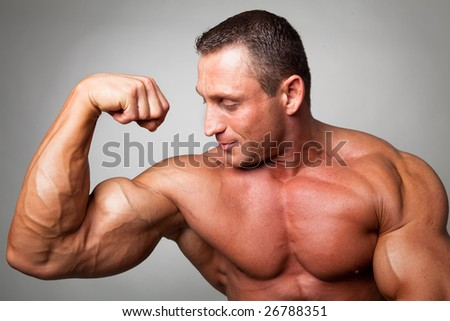 Muscular man flexing his biceps on gray background - stock photo
