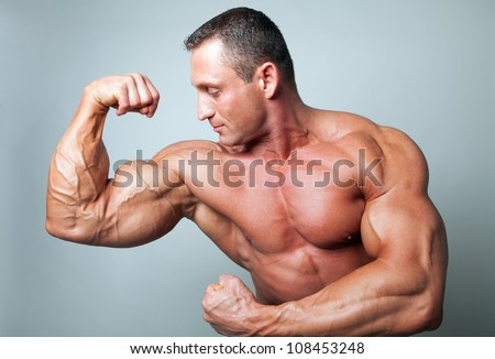 Muscular man flexing his biceps - studio shot - stock photo