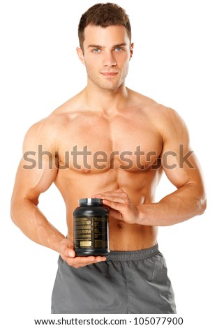 Muscular man holding black container of training supplements