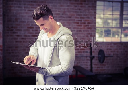 Muscular man holding clipboard at the gym - stock photo