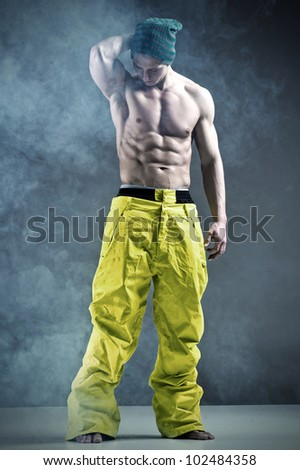 Muscular man in a fashion pose in snowboard trousers - stock photo