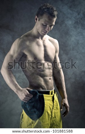 Muscular man in a fashion pose with cap - stock photo