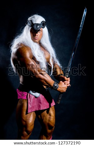 Muscular man in an image of a barbarian with a raised sword. Against a dark background