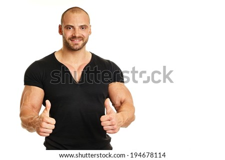 Muscular man in black shirt showing thumbs up. With copy space. - stock photo