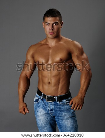 Muscular man in blue jeans on a gray background - stock photo