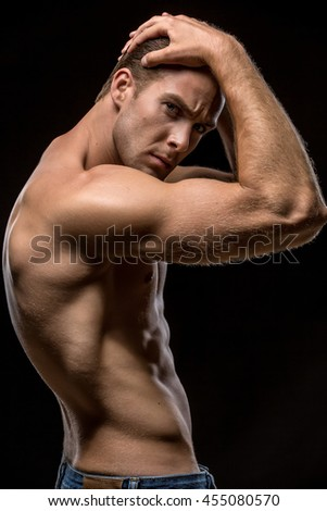Muscular man in blue jeans with naked torso stands sideways on the black background in the studio. He holds his hands on the head and looks into the camera. Vertical low-key photo.