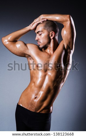 Muscular man in dark studio - stock photo