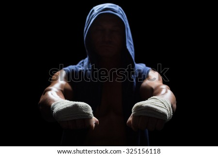 Muscular man in hood with bandage on hand against black background - stock photo