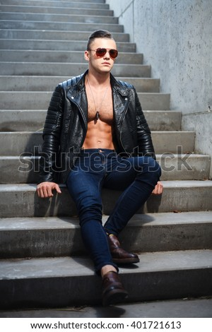 Muscular man in leather jacket and sunglasses sitting on stairs.