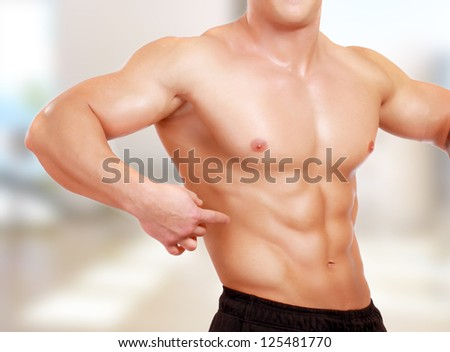 Muscular man in the gym centre - stock photo