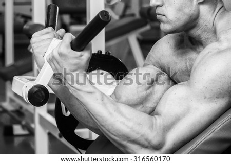 Muscular man in the gym. Work on the arm muscles. Training on a simulator. Exhausting work on his body. - stock photo