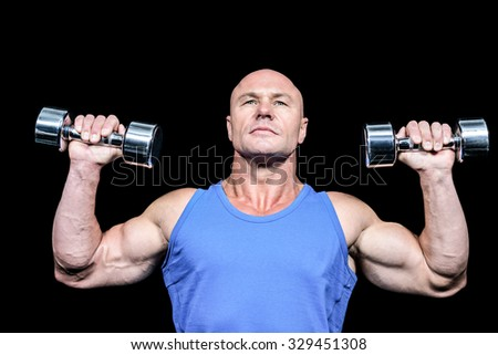 Muscular man in vest lifting dumbells against black background - stock photo