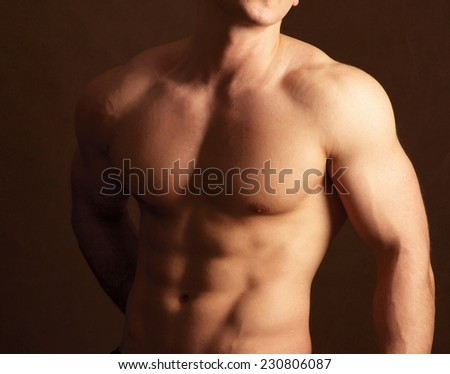 Muscular man , isolated on brown background