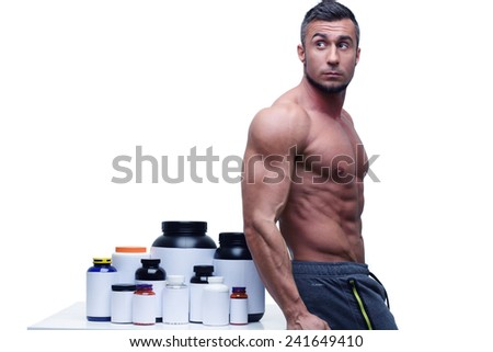 Muscular man leaning on the table with sports nutrition