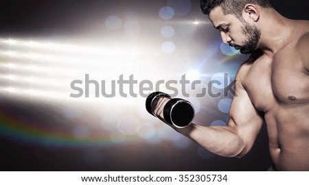 Muscular man lifting a dumbbell against lens flare