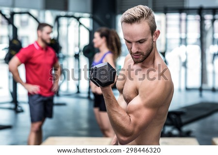 Muscular man lifting a dumbbell while looking at his biceps - stock photo