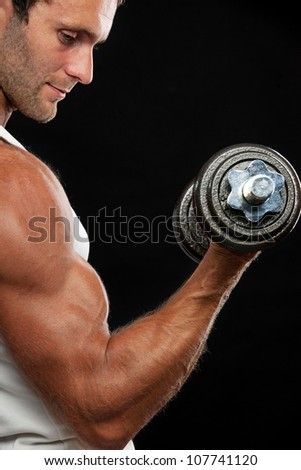 Muscular man lifting dumbbell on black background - stock photo