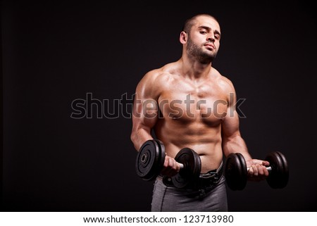 Muscular man lifting dumbbells isolated on black background