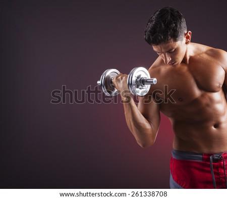 Muscular man lifting dumbbells on black background - stock photo