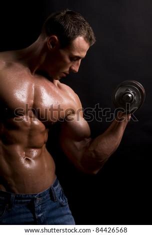Muscular man lifting weight - stock photo
