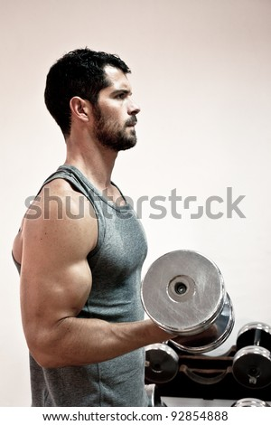 Muscular man lifting weights. Side view. - stock photo
