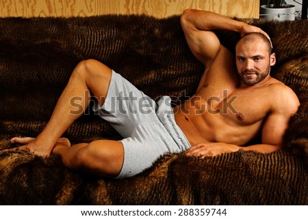 Muscular man lying on couch and relaxes - stock photo