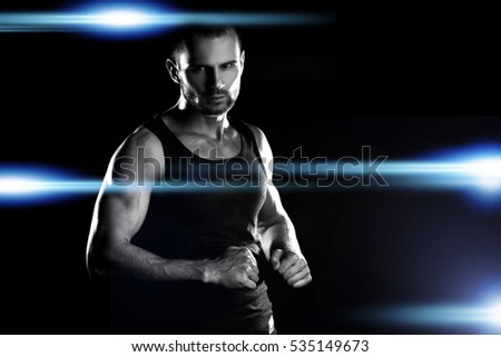 muscular man on a black background, clasps hands in a fist