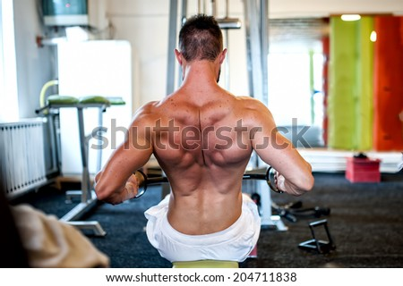 muscular man on daily workout routine at gym, close-up of back exercise - stock photo