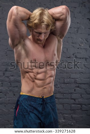 Muscular man on dark background brick wall. Bodybuilder. Strong man. Healthy muscular young man with his arms lift up on gray brick wall background. Copy space for text. Posters, advertising for gym.