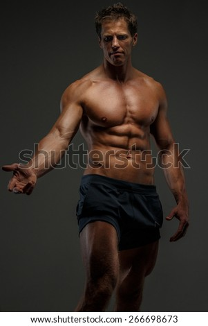 Muscular man posing in studio isolated on grey