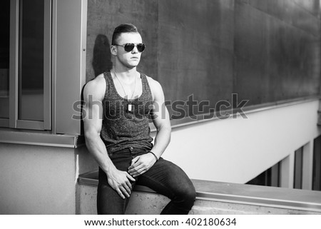 Muscular man posing near building. Black and white. - stock photo