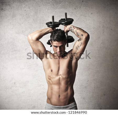 Muscular man raising behind his head two dumbbells - stock photo