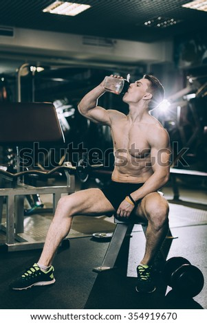 Muscular Man Resting After Exercise And Drinking Water - stock photo