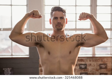 Muscular man showing biceps at the gym - stock photo