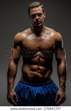 Muscular man showing his chest and stomach. Isolated on grey