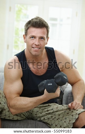 Muscular man sitting at home on sofa, doing excercise with hand barbell. - stock photo