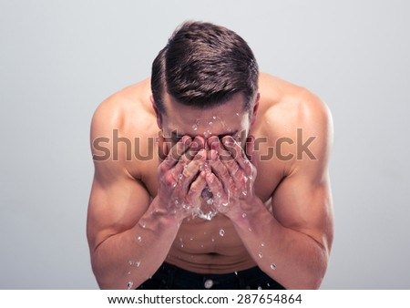 Muscular man spraying water on his face over gray background - stock photo
